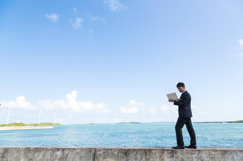 沖縄の海岸でパソコンを触る男性